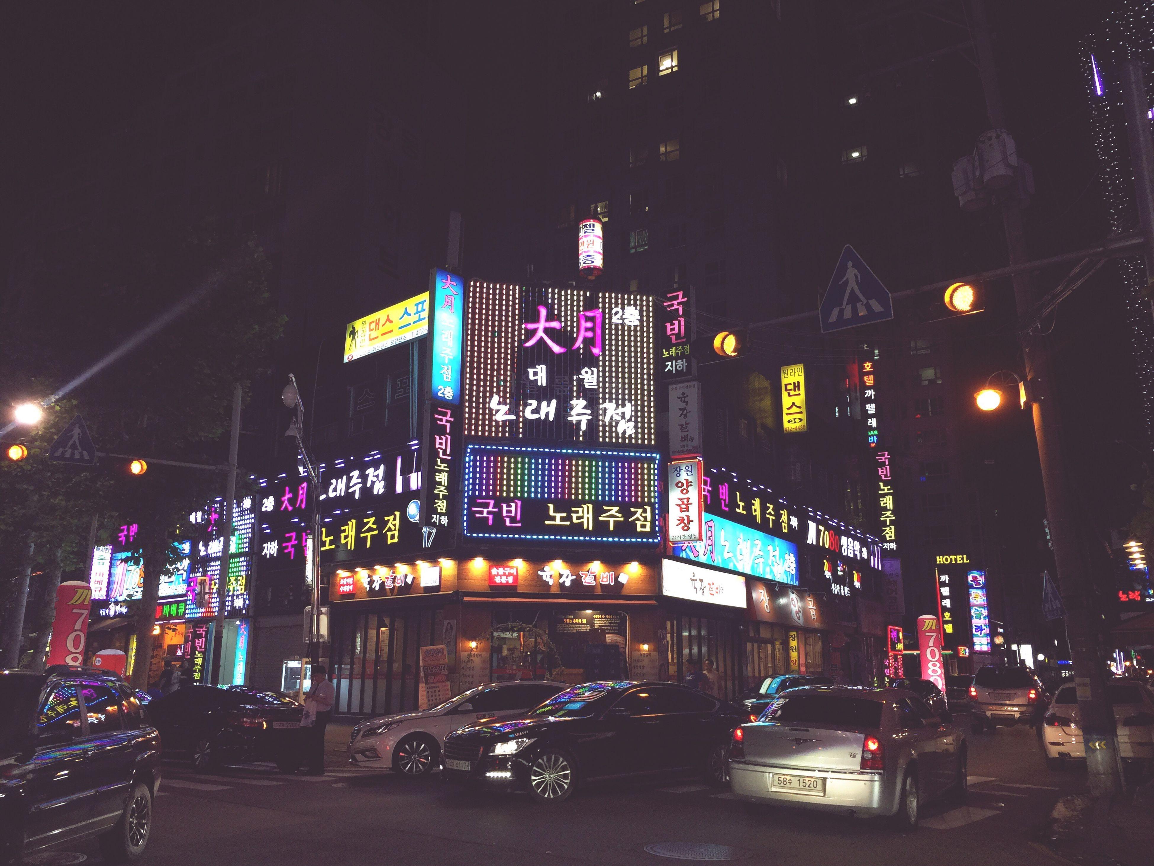 illuminated, night, architecture, built structure, city, city life, street light, city street, road, outdoors, sky, travel destinations, modern, information sign, dark