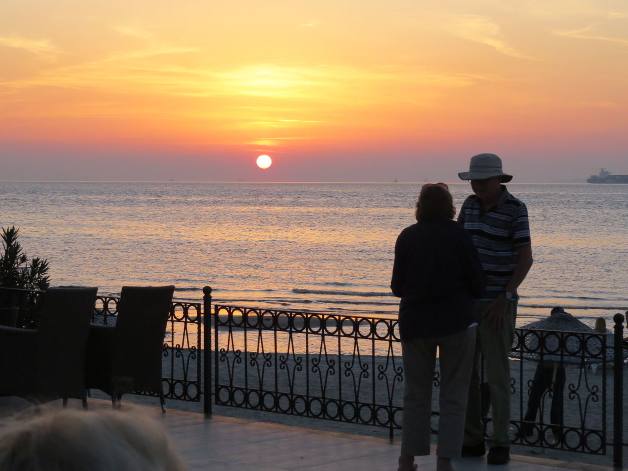 sunset, sea, rear view, real people, two people, horizon over water, water, nature, togetherness, beauty in nature, railing, standing, scenics, sky, love, leisure activity, men, tranquil scene, full length, outdoors, beach, women, lifestyles, friendship, day, people