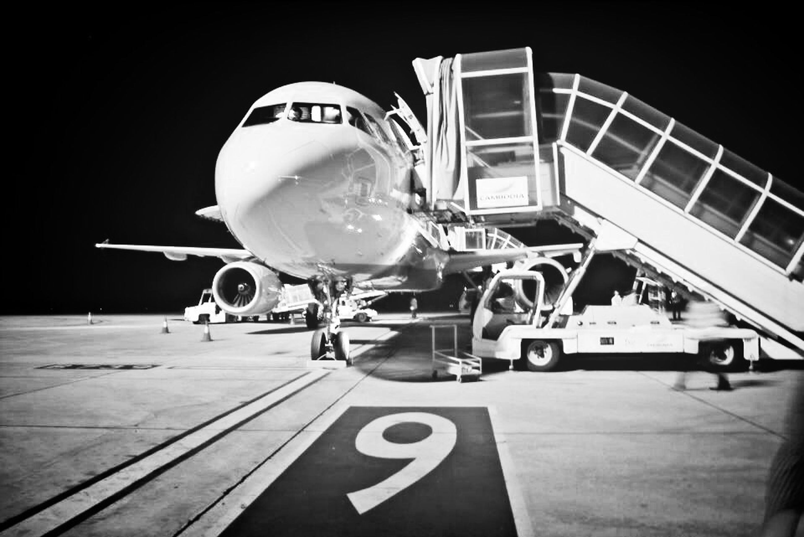 transportation, architecture, built structure, airplane, air vehicle, mode of transport, building exterior, airport, communication, city, low angle view, day, guidance, modern, text, clear sky, outdoors, lighting equipment, travel, western script