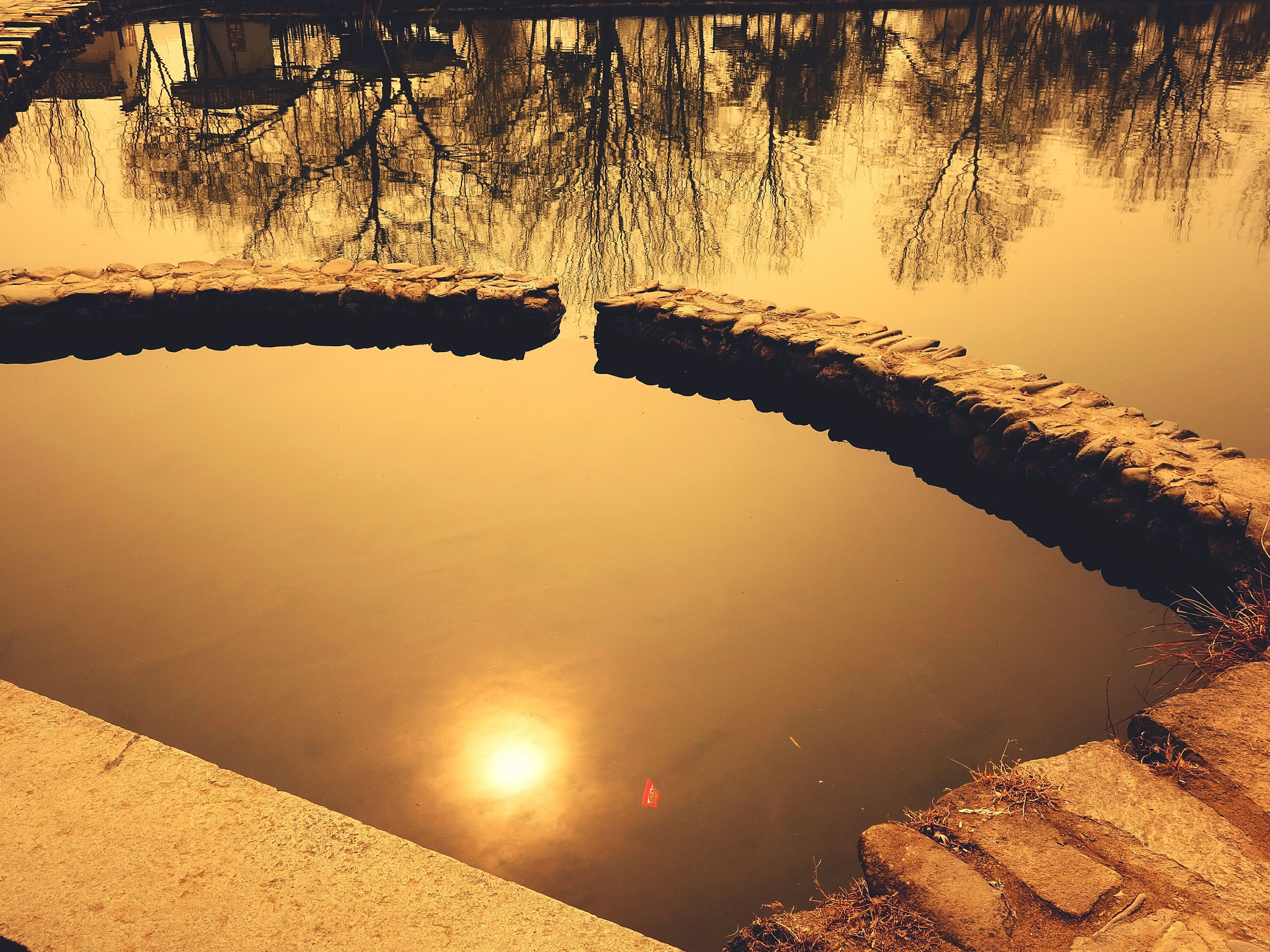 water, reflection, tranquility, tranquil scene, nature, tree, sunset, scenics, beauty in nature, lake, sunlight, silhouette, standing water, built structure, sky, outdoors, no people, high angle view, idyllic, sun