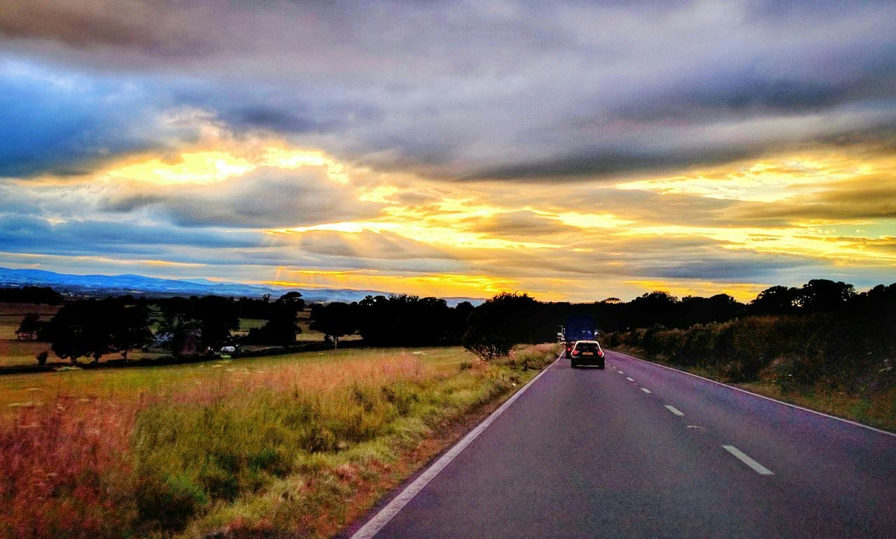 road, the way forward, sunset, transportation, sky, cloud - sky, car, nature, no people, scenics, landscape, land vehicle, tranquil scene, beauty in nature, tranquility, outdoors, tree, grass, day