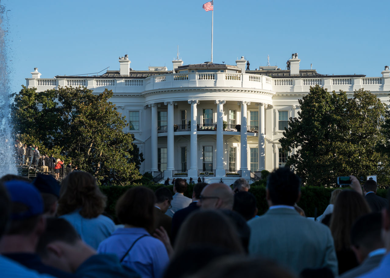 Rear View Of People Standing In Front Of White House