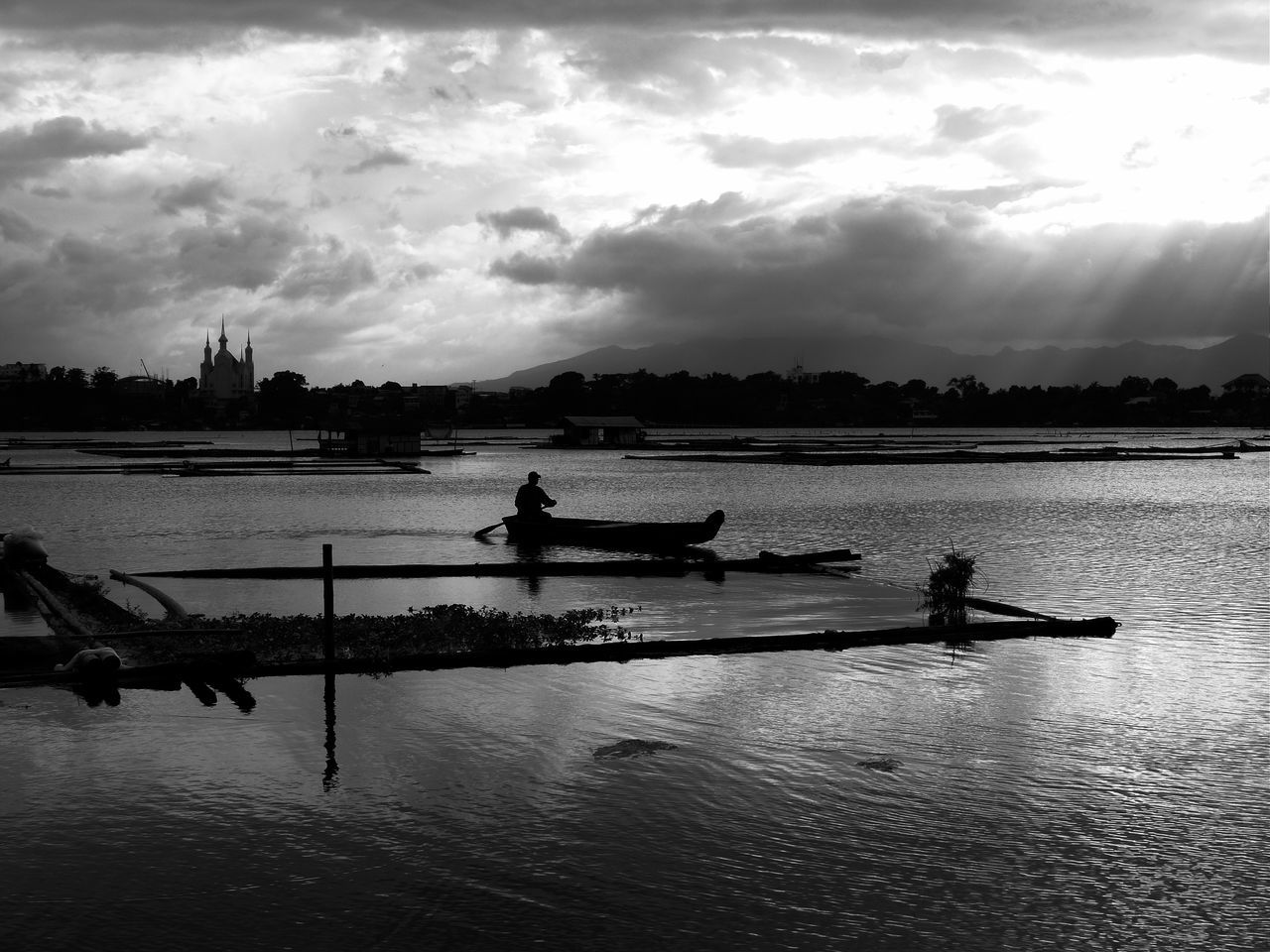 nautical vessel, water, transportation, cloud - sky, mode of transport, sky, boat, real people, river, rowing, men, one person, outdoors, silhouette, oar, nature, canoe, day, sitting, outrigger, one man only, people