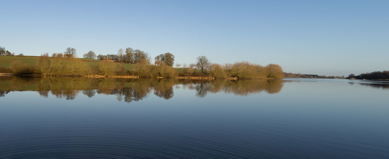 reflection, tranquil scene, nature, tranquility, scenics, lake, water, beauty in nature, tree, outdoors, idyllic, clear sky, no people, waterfront, blue, day, sky