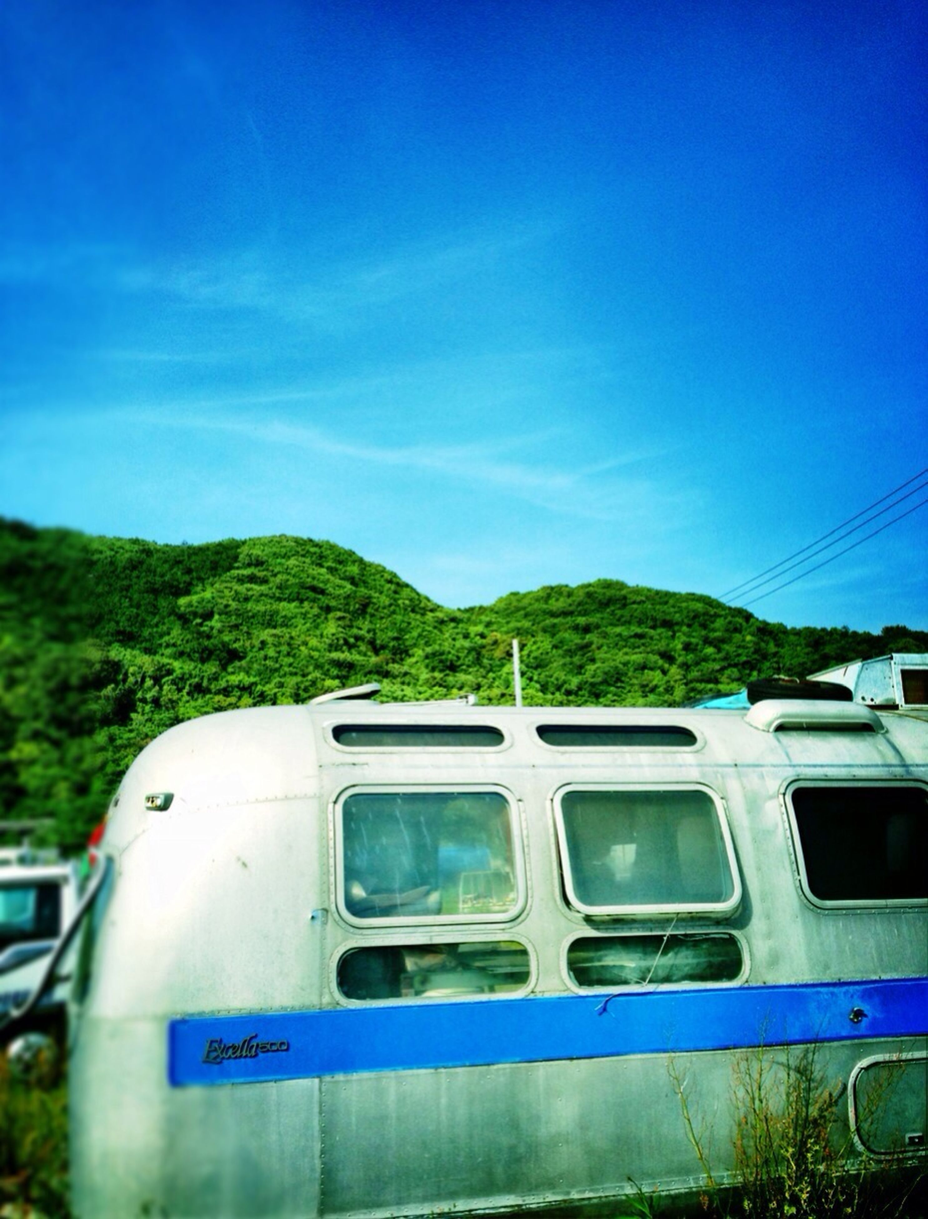 blue, transportation, mountain, mode of transport, clear sky, sky, day, land vehicle, nature, tree, rail transportation, outdoors, train - vehicle, no people, public transportation, travel, built structure, car, copy space, railroad track