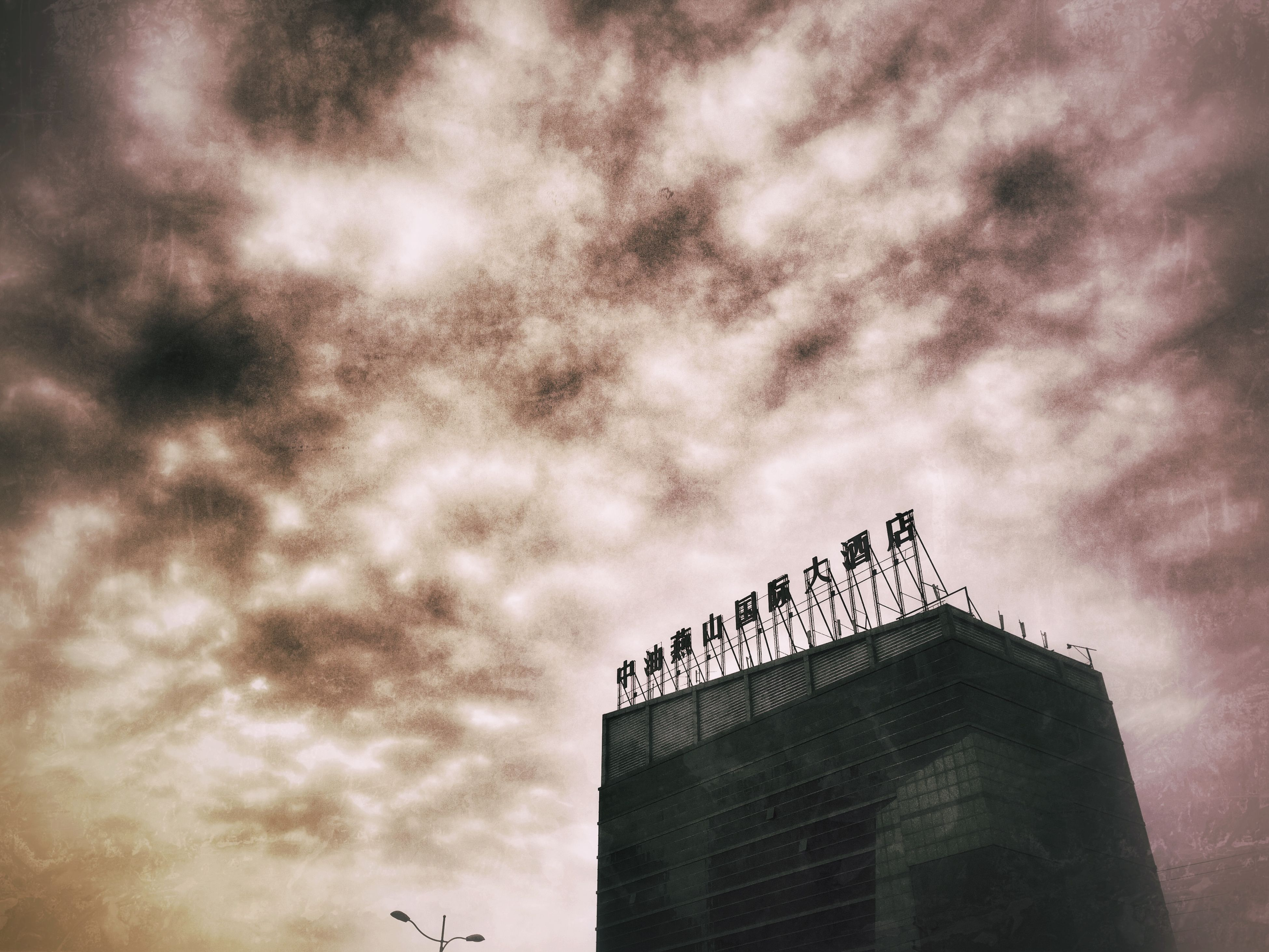 low angle view, sky, built structure, architecture, building exterior, cloud - sky, cloudy, bird, overcast, outdoors, day, cloud, high section, no people, weather, communication, building, animal themes, text, animals in the wild