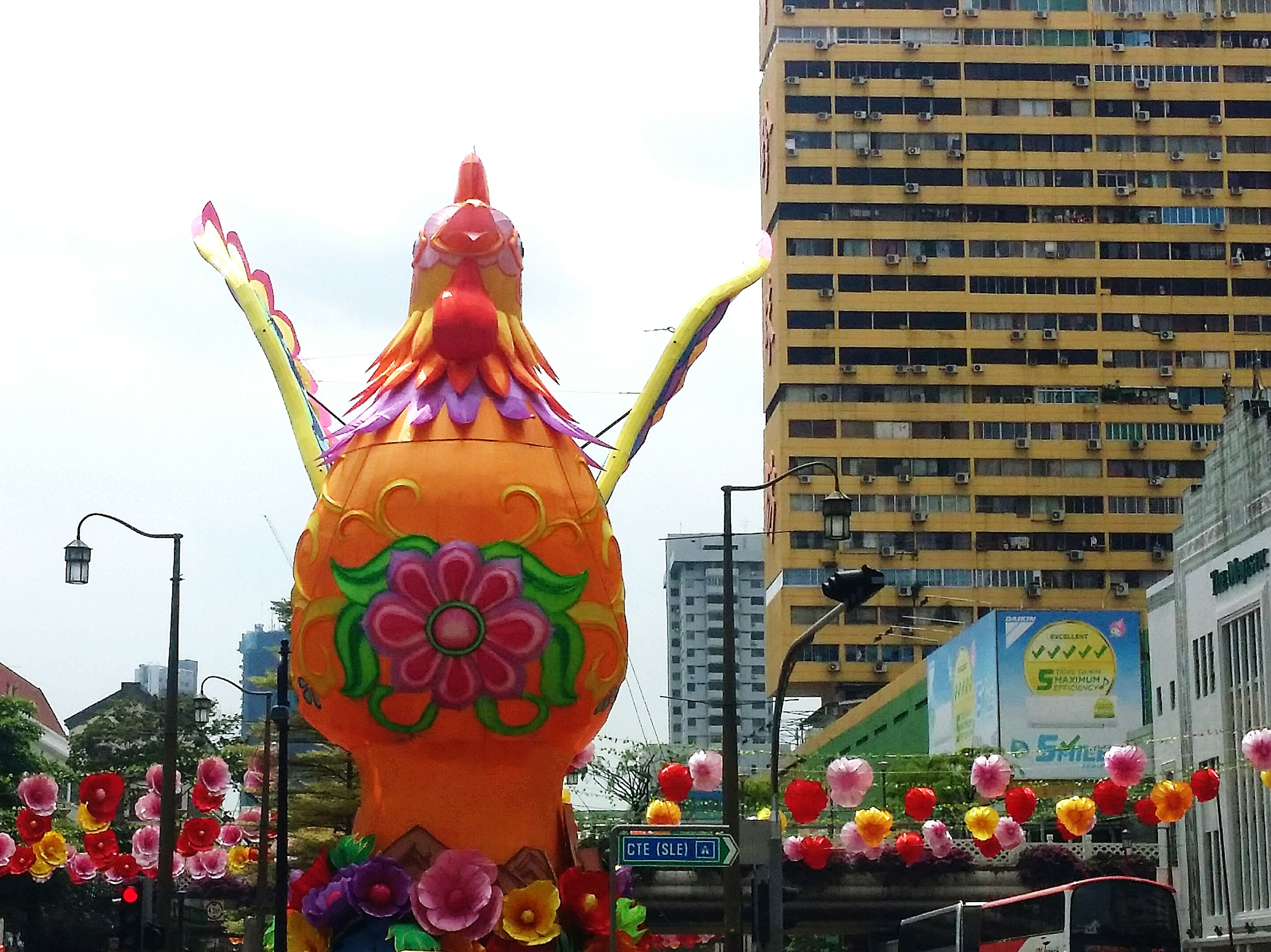 city, building exterior, architecture, statue, travel destinations, celebration, built structure, outdoors, chinese new year, sky, large group of people, sculpture, cityscape, chinese lantern festival, skyscraper, day, people, annual event, astrology sign
