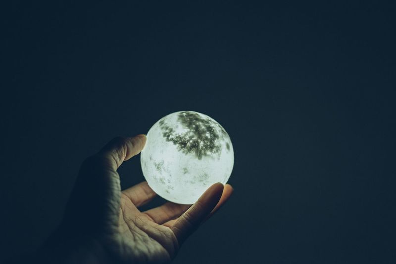 Astronomy Black Background Close-up Crystal Ball Globe Holding Human Body Part Human Hand Moon Nature One Person Outdoors People Planet - Space Planet Earth Planetary Moon Real People Solar Eclipse Space Space Exploration Sphere