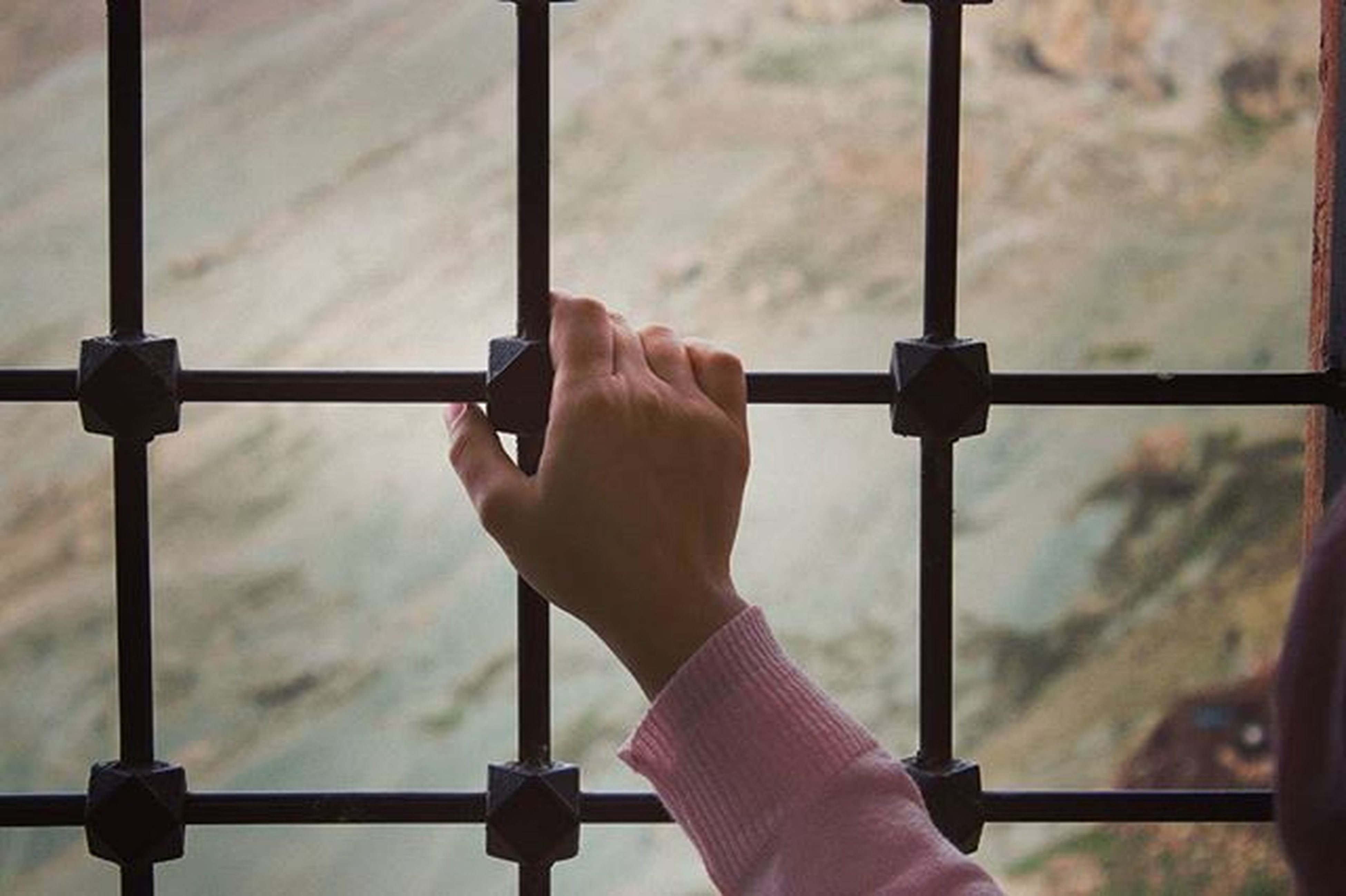 person, holding, metal, lifestyles, part of, leisure activity, focus on foreground, men, human finger, indoors, cropped, day, protection, close-up, railing, safety, sky