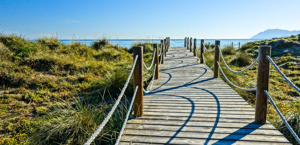 Krull&Krull Images Mallorca Railing WAOOOWW Beach Beauty In Nature Clear Sky Connection Day Grass Landscape Light And Shadow Nature No People Outdoors Railing Scenics Sky Son Serra De Marina Sunlight Walkway Water Waterfront Way Wood - Material An Eye For Travel