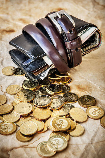 Wallet tied with belt and gold coins spilled on grungy brown paper Assets Bailout Banking Belt  Belt Tightening Budget Close-up Coins Concept Economy Gold Coins Grungy Income Liabilities Money Mortgage Paper Personal Finance Savings Spending Spilled Still Life Thrift Tied Wallet