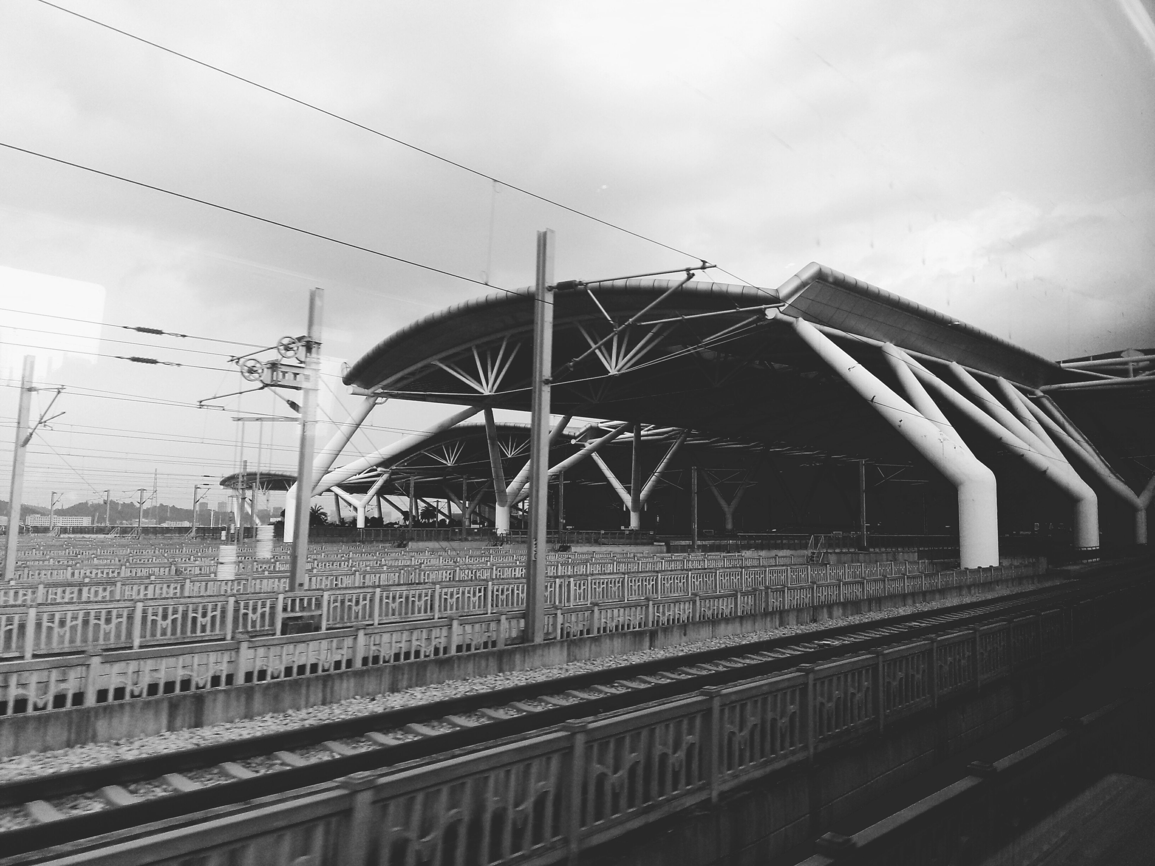 architecture, built structure, sky, low angle view, building exterior, railing, connection, cloud - sky, rail transportation, day, bridge - man made structure, transportation, railroad station, no people, outdoors, railroad track, cloudy, building, cloud, diminishing perspective