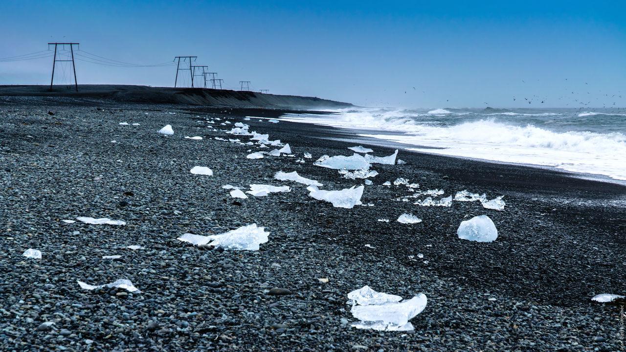 Close-Up Iceberg On Beach Against Sky