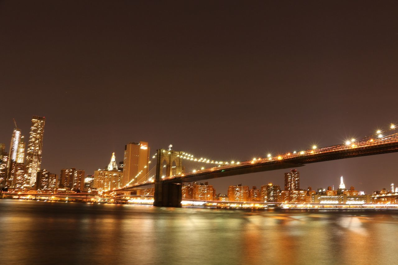 Illuminated Brooklyn Bridge Over River Against Sky At Night