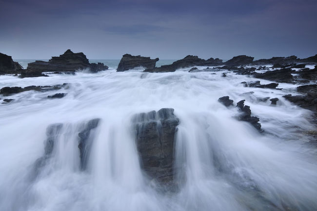 Wave Flow at Sawarna Beach, Indonesia During Cloudy Beauty In Nature Blue Day Flowing Flowing Water Idyllic Majestic Motion Nature No People Non-urban Scene Outdoors Power In Nature Rock - Object Rock Formation Scenics Sky Splashing Tourism Tranquil Scene Tranquility Travel Destinations Water Waterfall Wave