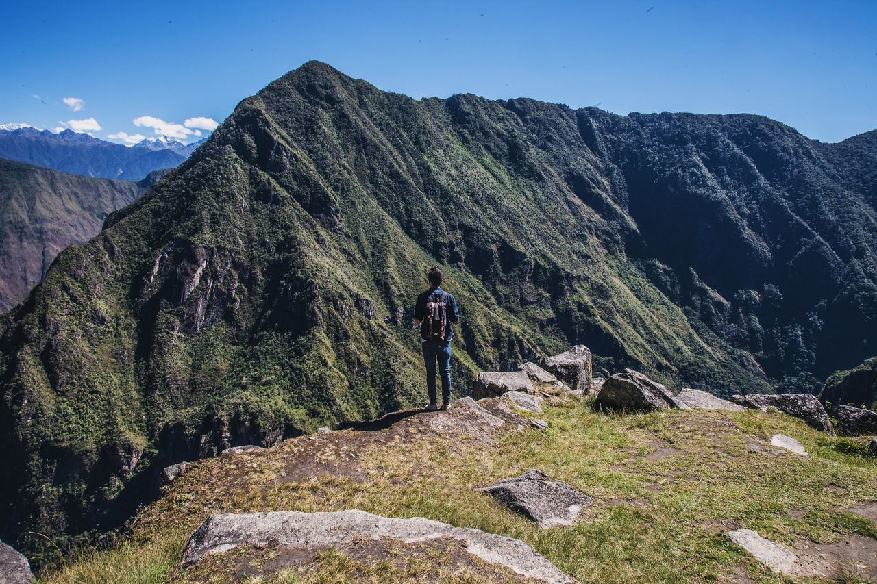Man Looking At Mountains From Cliff