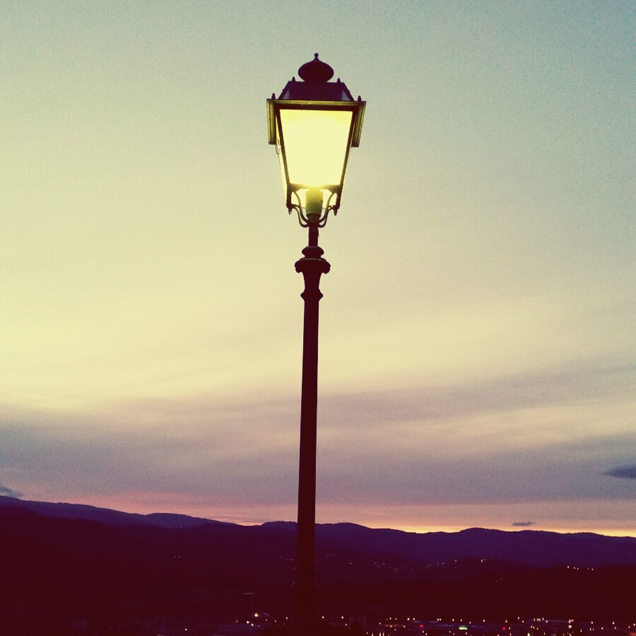 street light, lighting equipment, sky, nature, sunset, beauty in nature, outdoors, scenics, no people, illuminated, tranquility, street lamp, silhouette, tranquil scene, mountain, low angle view, day