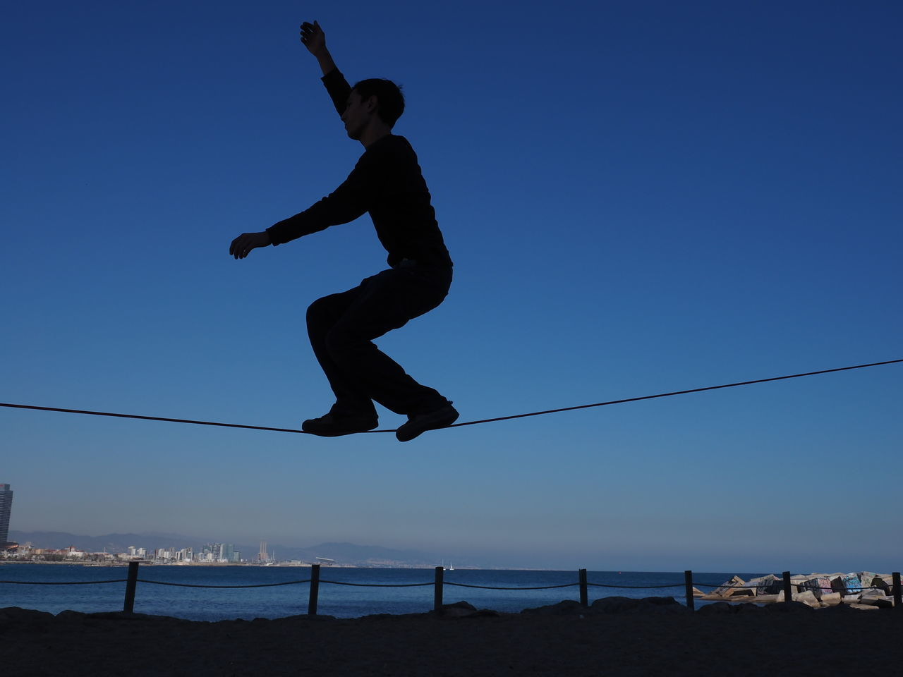 Man On Tightrope At Beach Against Clear Blue Sky