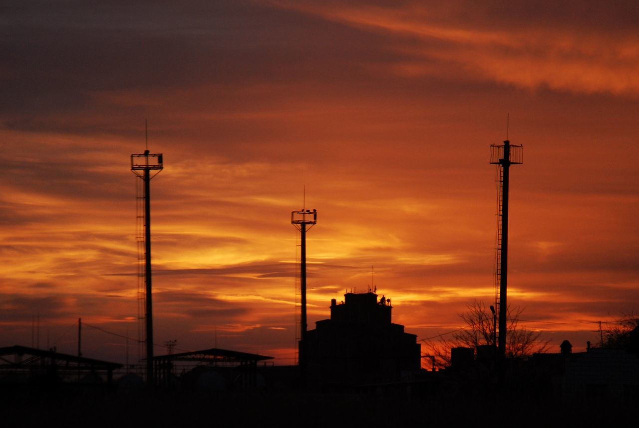 Silhouette Lookout Towers Against Orange Sky