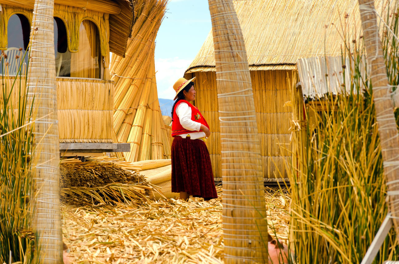 UROS FLOATING ISLANDS, PERU - SEPTEMBER 18: Indigenous woman on the Uros Floating Islands, Peru on September 18, 2014 Adult Altitude Andes Coutryside Floating High Houses Inca Lake Landmark Manmade Nature Outdoors Puno Reed Rural Standing Sun Titicaca Titicaca Lake Totora Traditional Uros Uros Island Women