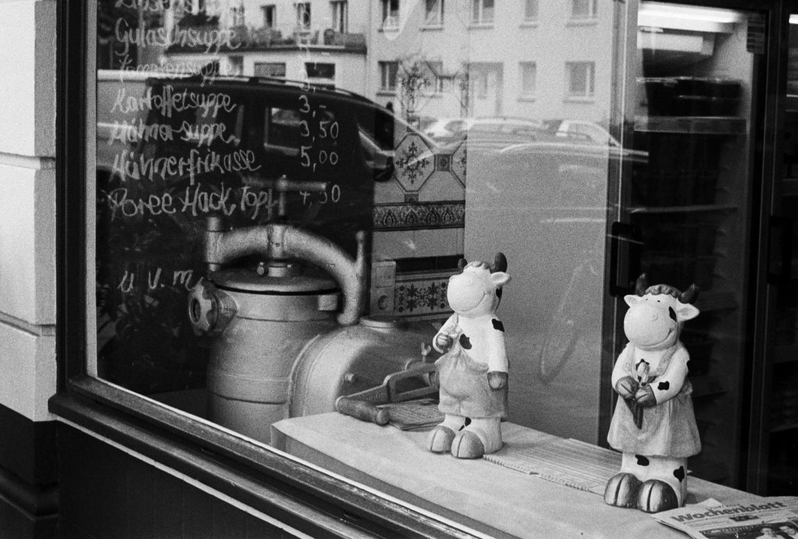 Zwei Zeiten, Contessa, Ilford HP5 400 35mm Analog Analogue Photography Black & White Black And White Butcher Chalkboard Childhood City Life Contessa Cows Day Indoors  Menu No People Store Window Street Streetphotography Stuffed Toy Text Urban Window
