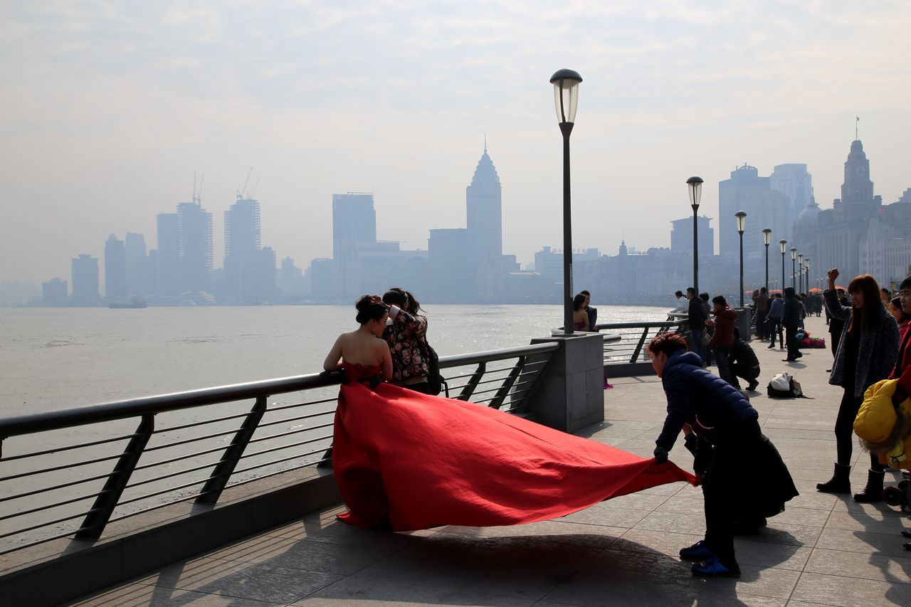 Marriage on the Bund in Shanghai in front of Pudong Skyline Adult Adults Only City Cityscape Couple Marriage Ph Day Full Length Gondola - Traditional Boat Marriage  Men Outdoors People Red Dress Red Lips Sky Street Light The Bund The Bund Shanghai Togetherness Train Ride Travel Destinations Two People Urban Skyline Woman Young Adult