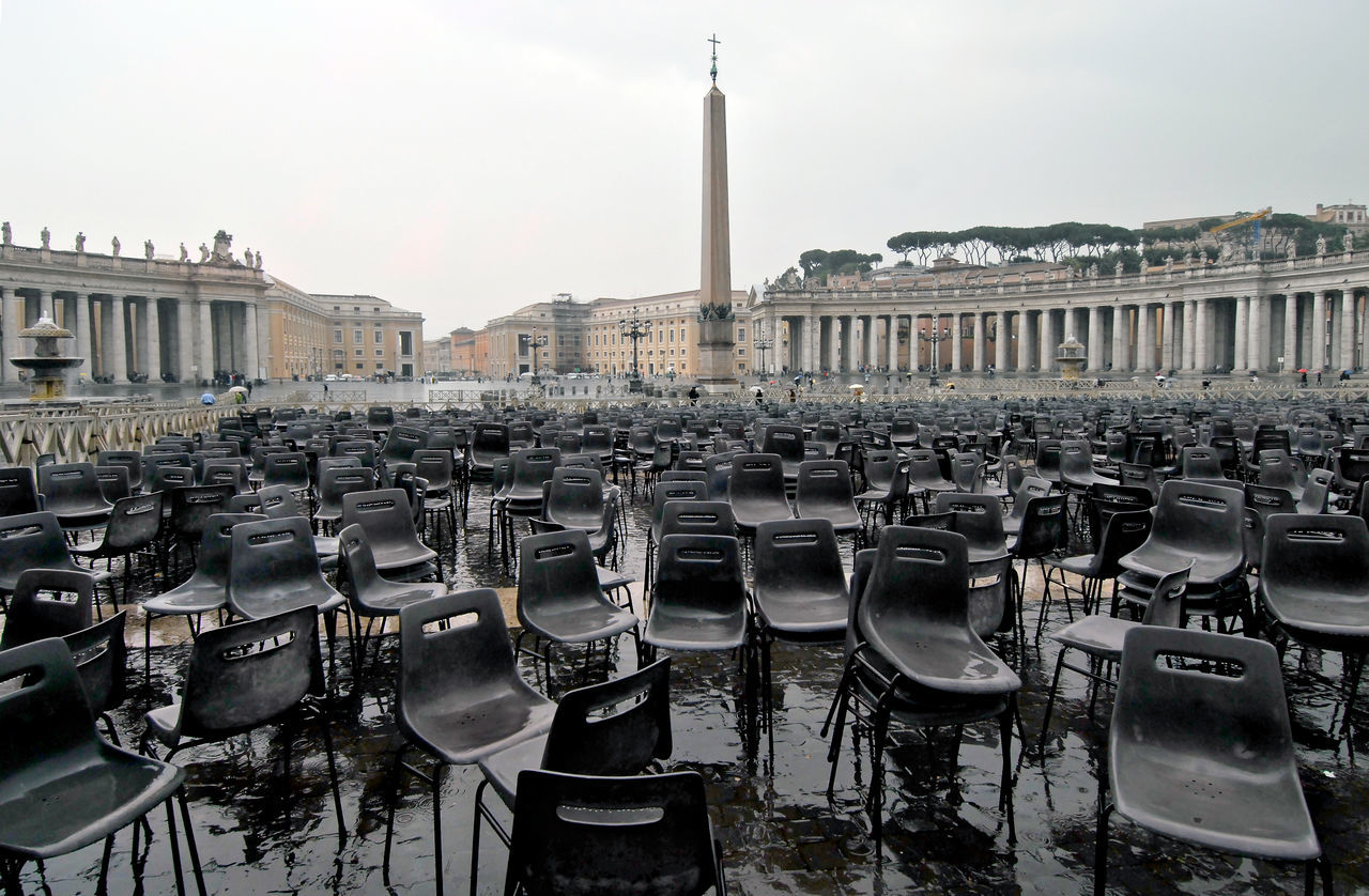 Italy, Rome, St. Peter's after mass Absence Arrangement Chair City Life Community Culture Empty Furniture Human Settlement In A Row Large Group Of Objects No People Order Perspective Repetition Residential District Restaurant Seat Side By Side Sidewalk Cafe Table