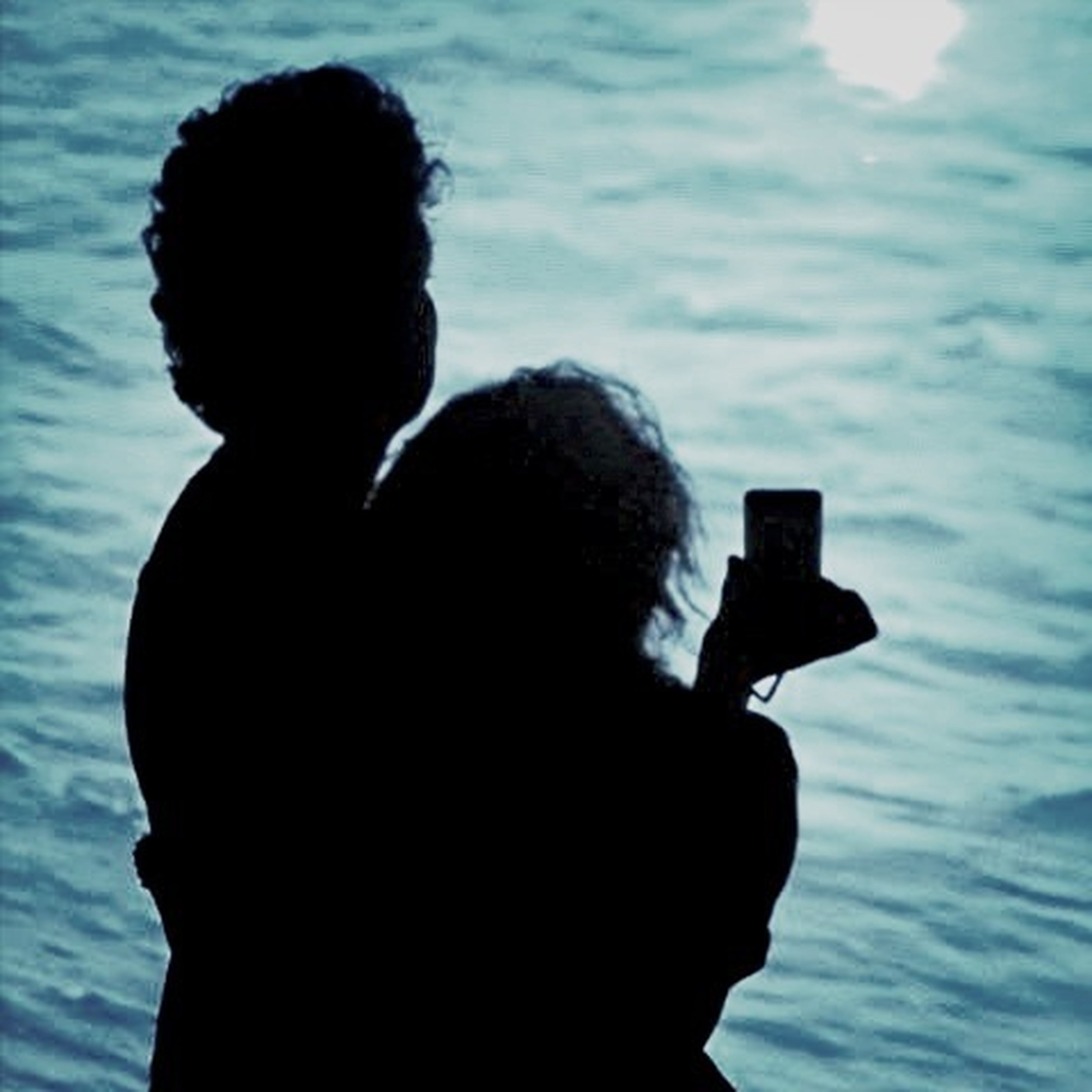 water, silhouette, men, lifestyles, leisure activity, sea, rear view, photography themes, photographing, focus on foreground, waist up, three quarter length, sky, technology, holding, headshot, camera - photographic equipment, standing