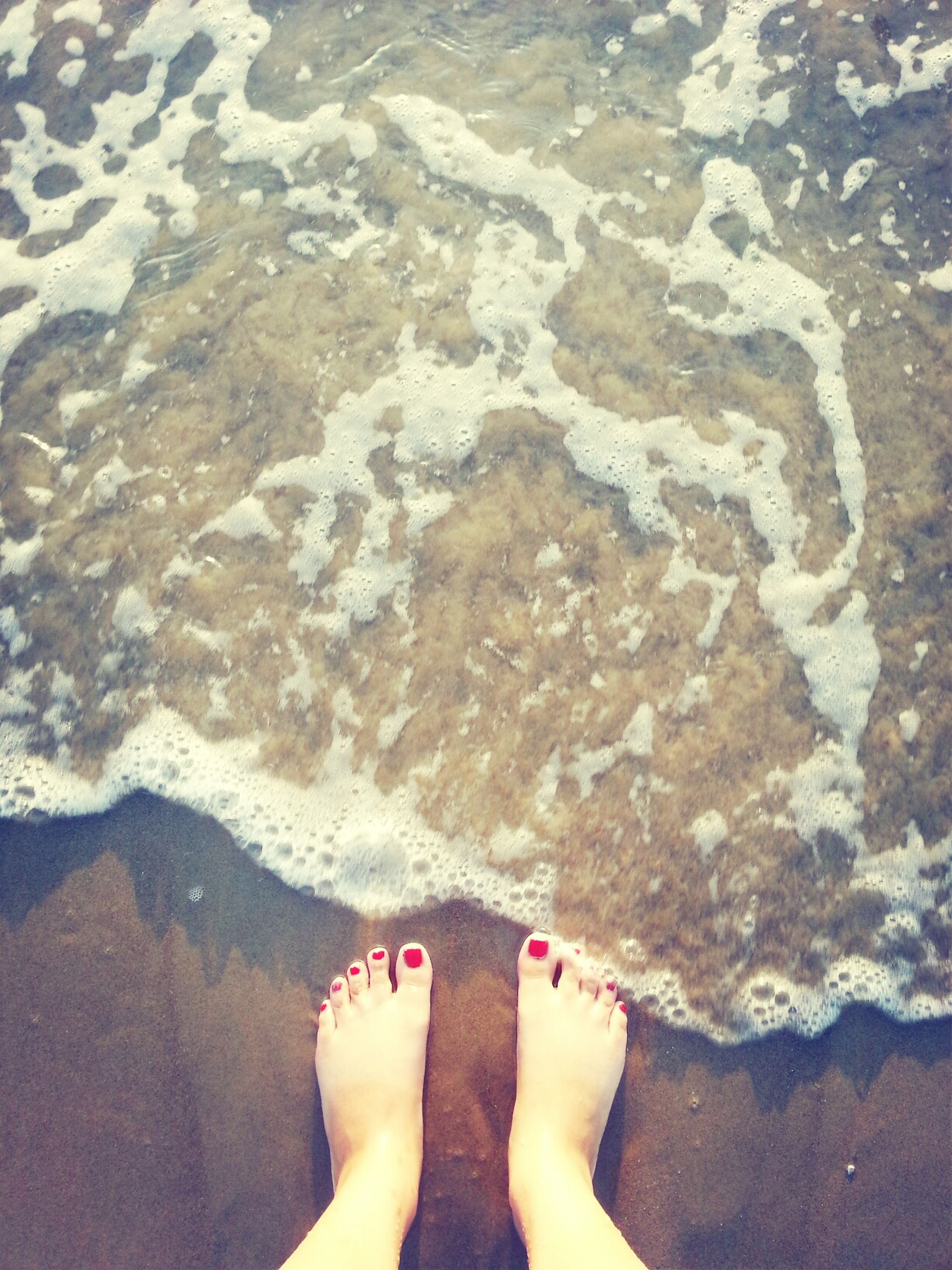 low section, person, water, beach, personal perspective, barefoot, human foot, sea, shore, sand, high angle view, leisure activity, standing, lifestyles, surf, vacations
