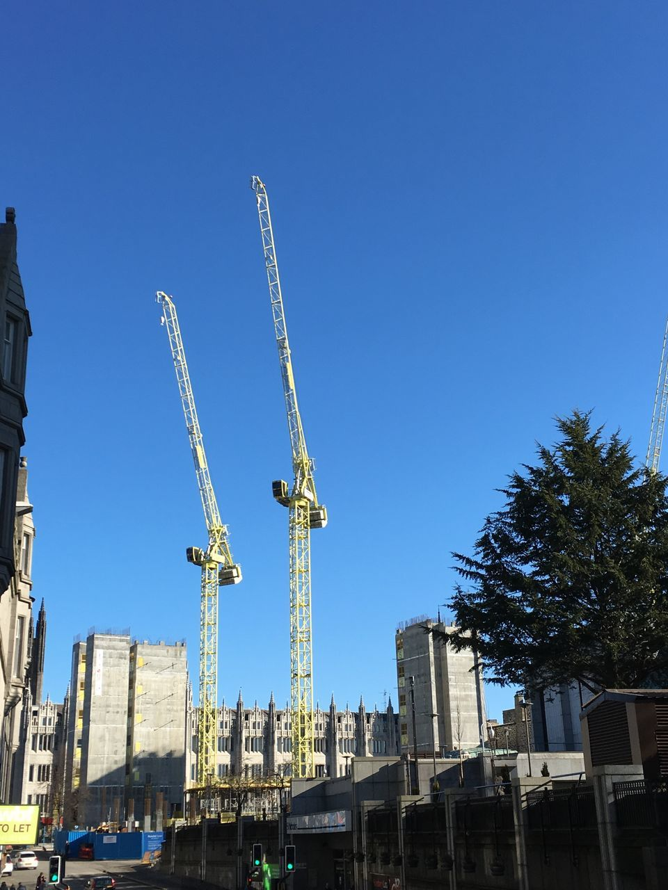 architecture, built structure, building exterior, blue, low angle view, development, clear sky, day, construction site, crane - construction machinery, no people, residential building, outdoors, progress, city, sky