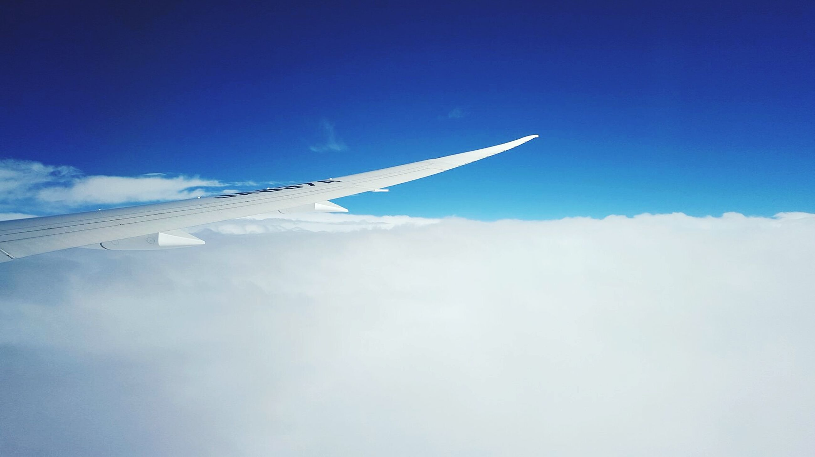 blue, airplane, flying, air vehicle, sky, transportation, low angle view, cloud - sky, mode of transport, aircraft wing, travel, vapor trail, mid-air, cloud, part of, cropped, journey, day, nature, on the move
