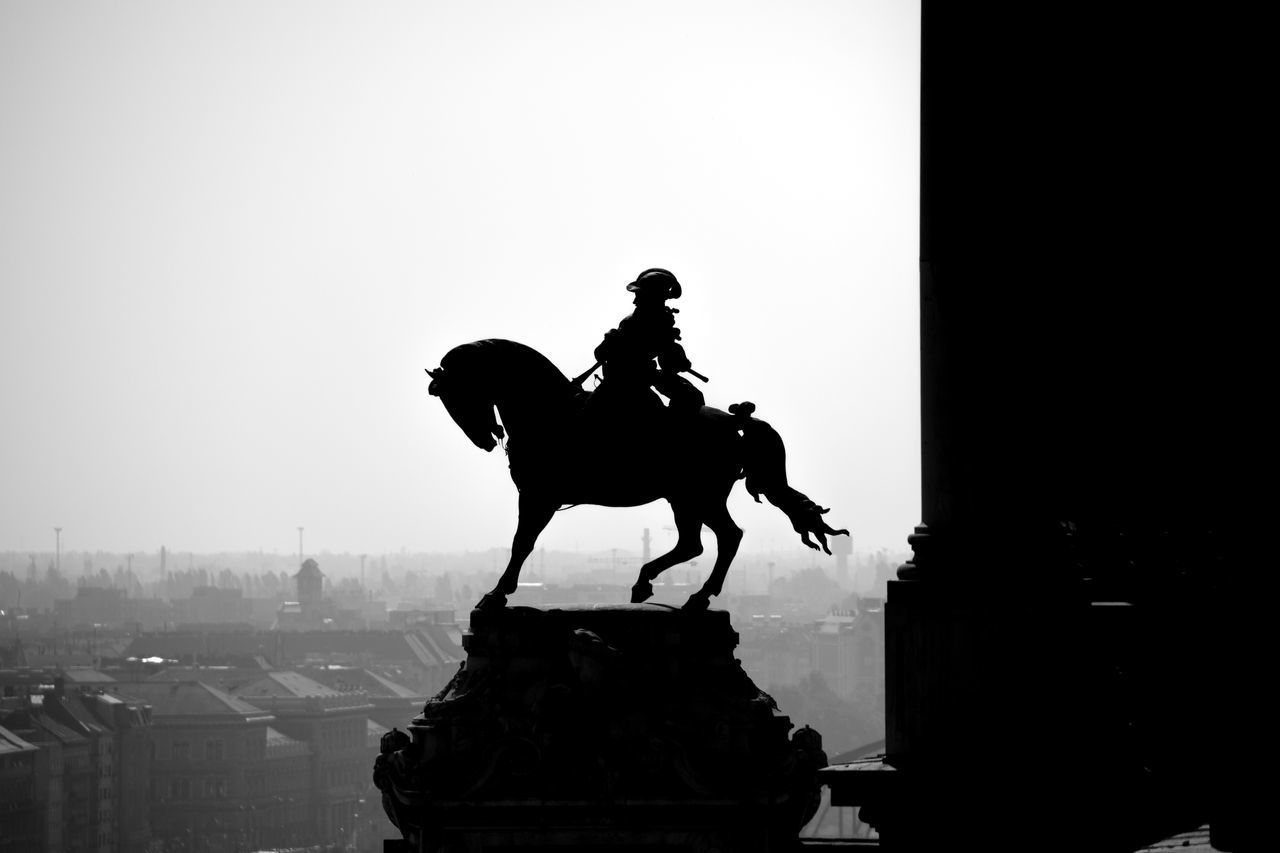 statue, horse, sculpture, horseback riding, human representation, monument, silhouette, city, riding, built structure, sky, clear sky, travel destinations, outdoors, king - royal person, architecture, men, real people, day, people