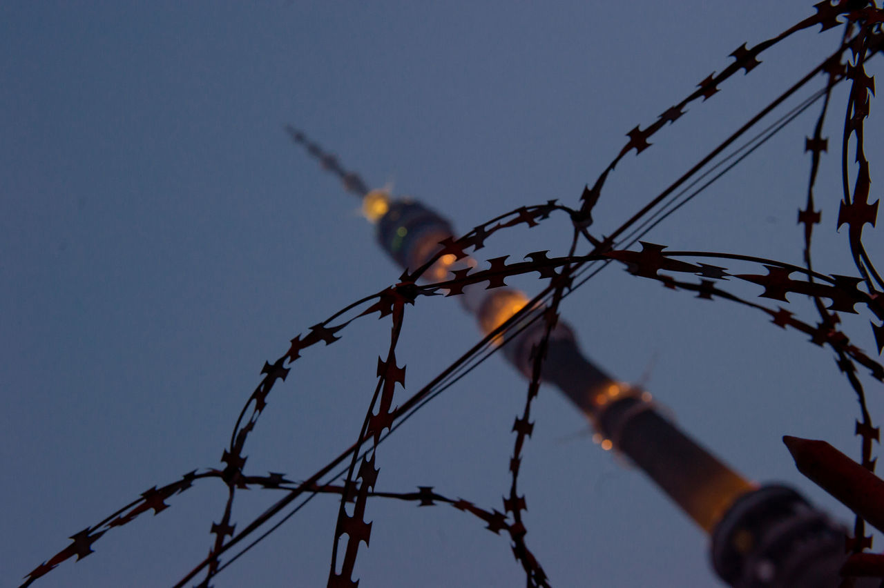 Low Angle View Of Razor Wire And Ostankino Tower Against Sky At Dusk
