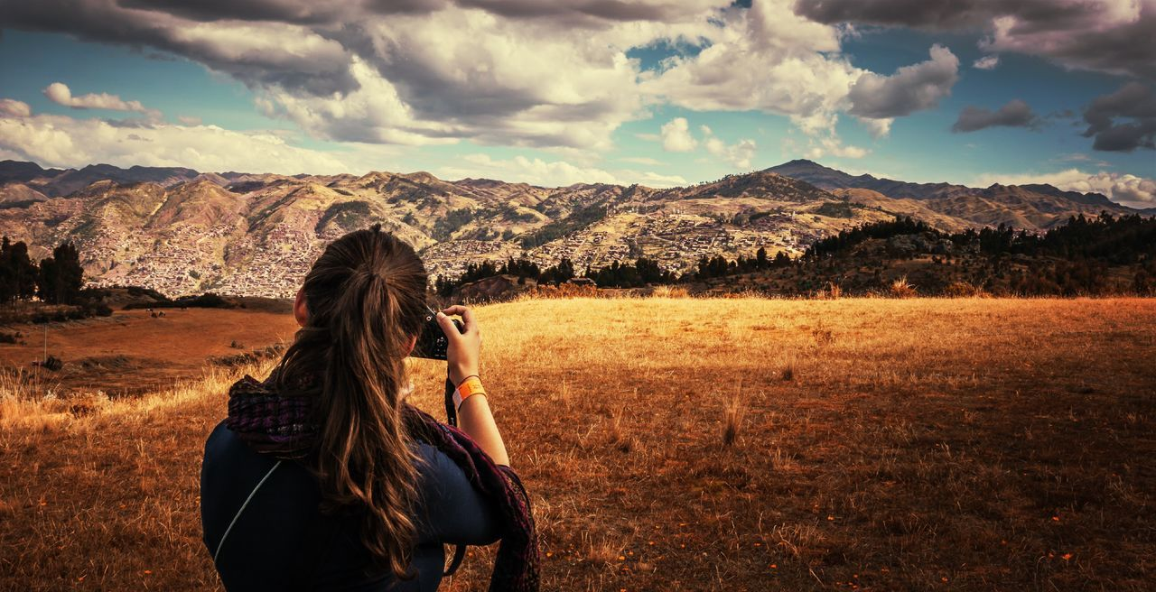 Rear View Of Woman Photographing Through Camera Against Mountains