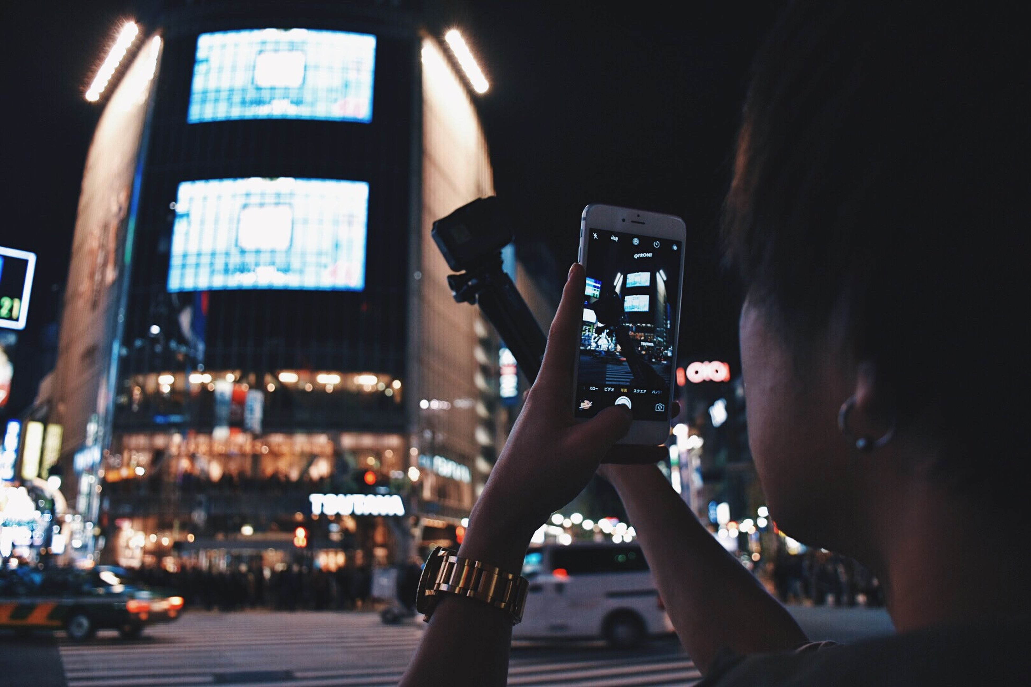 night, technology, illuminated, two people, rear view, photography themes, city, real people, adults only, people, outdoors, adult, filming