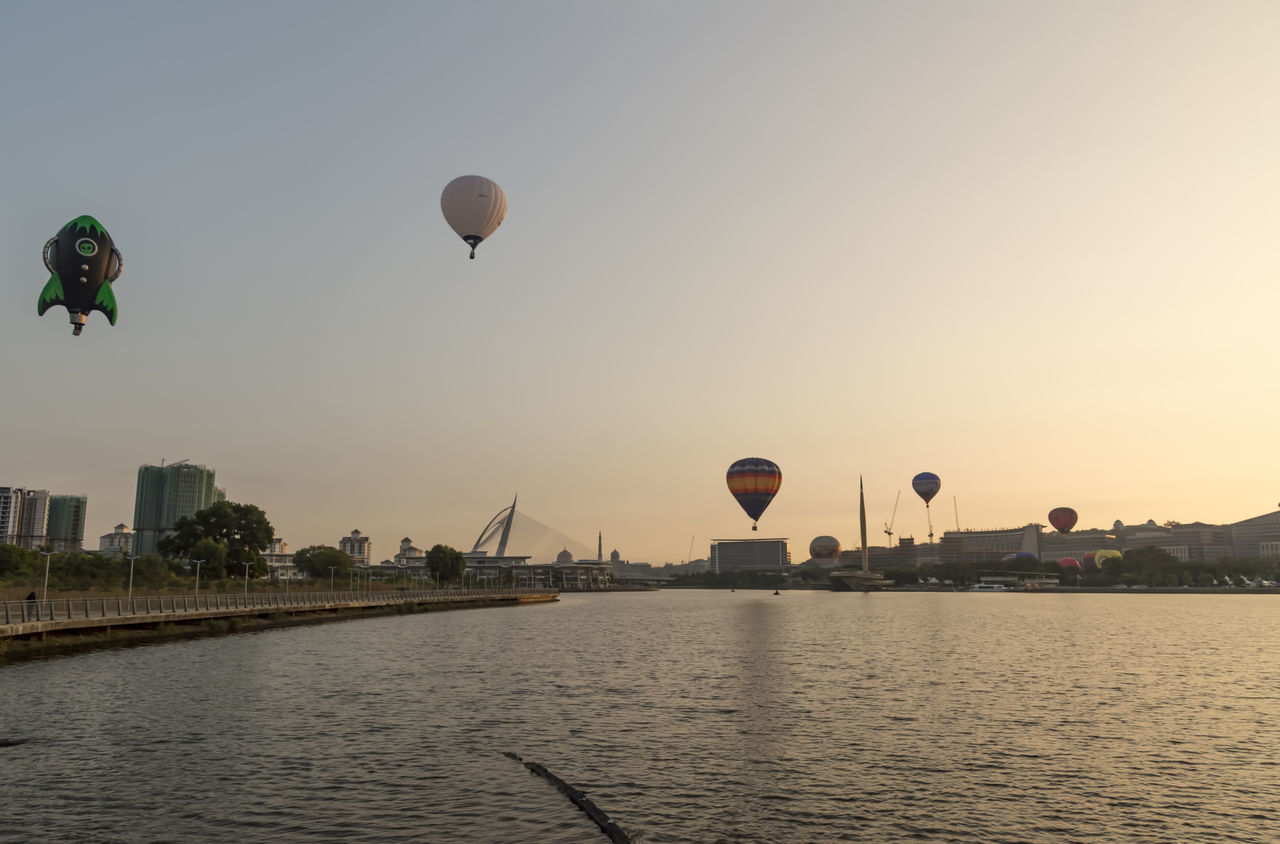 flying, river, mid-air, water, hot air balloon, waterfront, outdoors, sunset, built structure, nature, architecture, clear sky, no people, sky, day, city