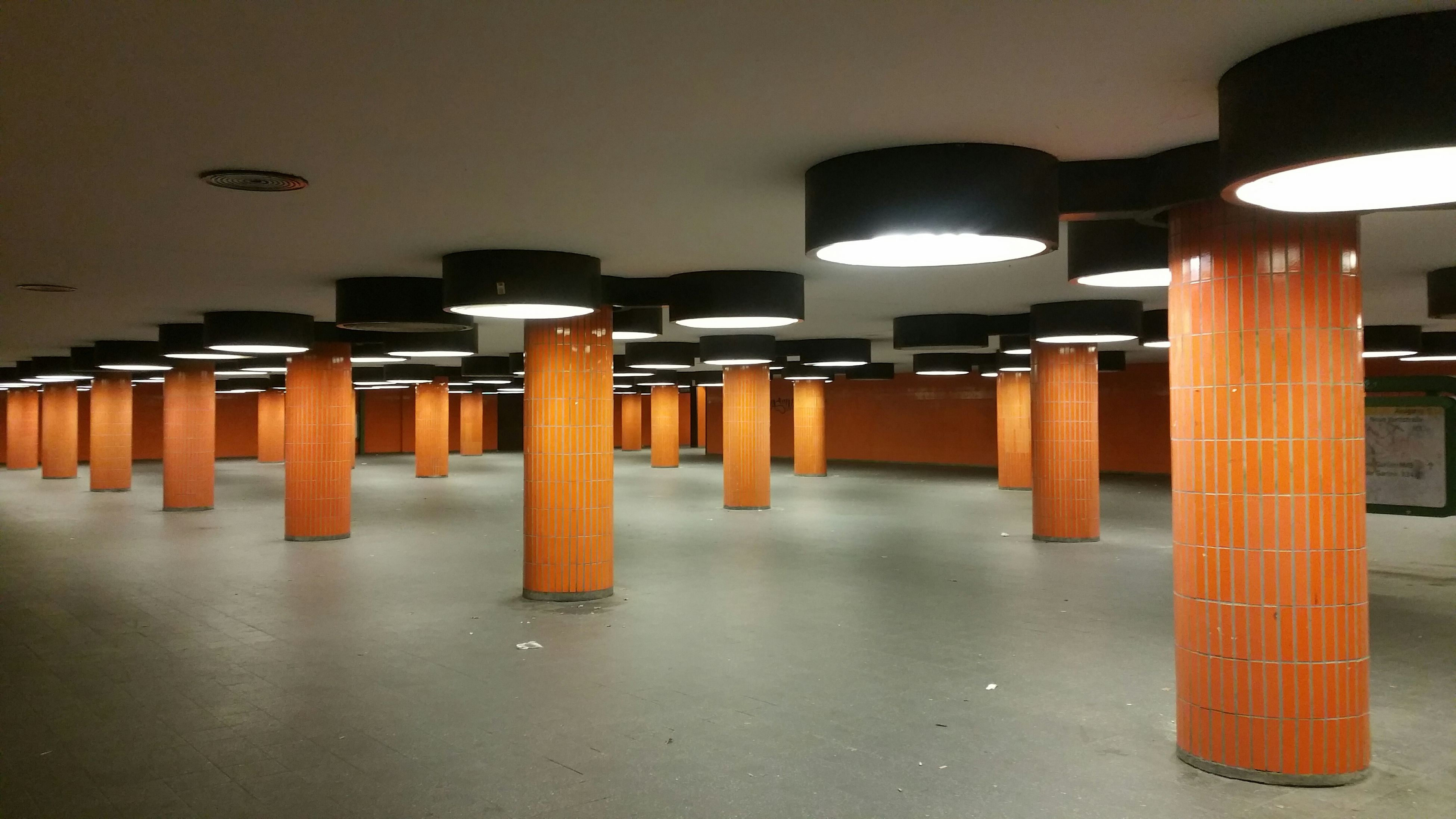 indoors, illuminated, in a row, built structure, architecture, architectural column, empty, column, corridor, lighting equipment, flooring, the way forward, ceiling, absence, pillar, repetition, diminishing perspective, orange color, arch, railing