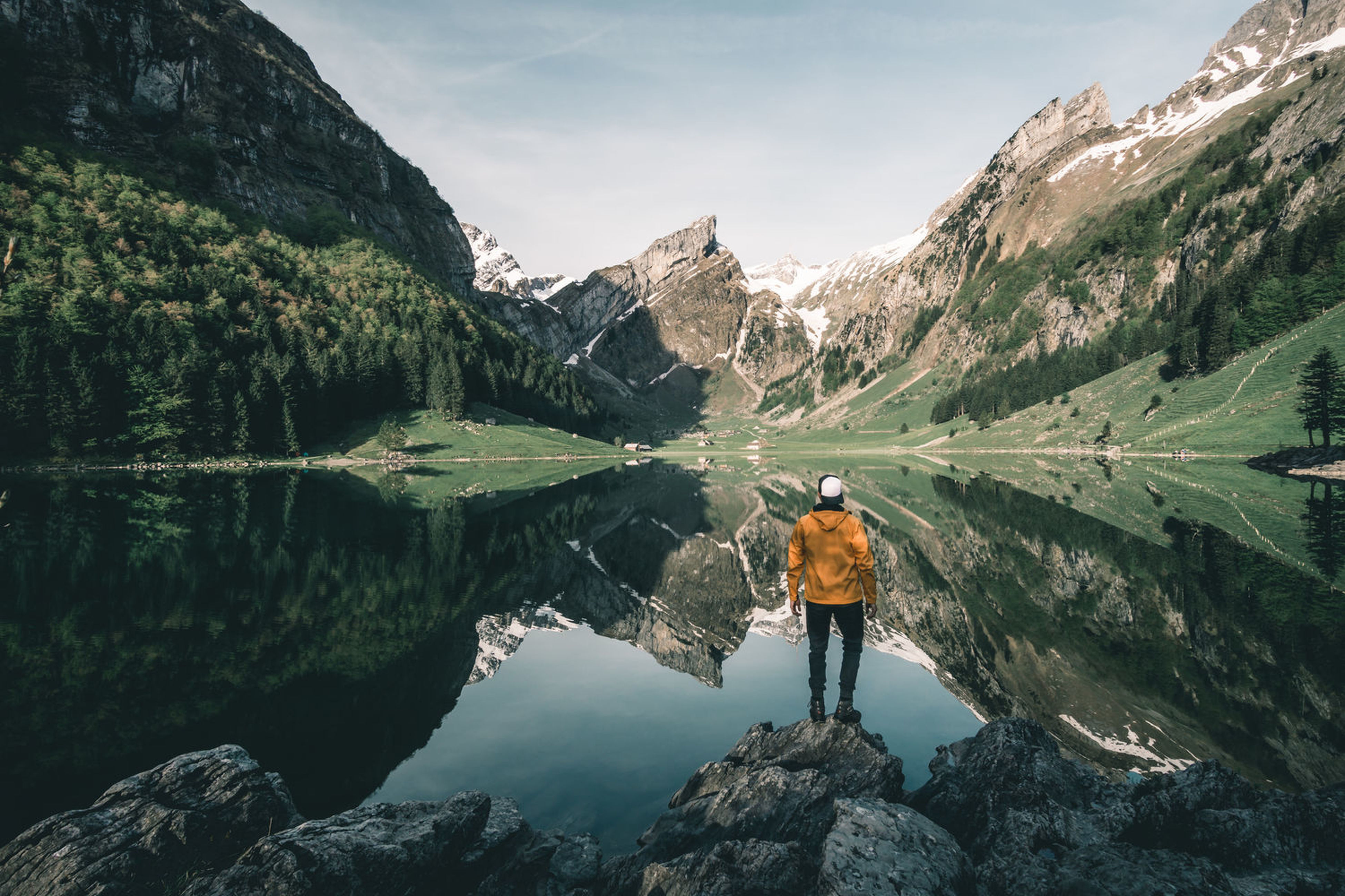 mountain, real people, nature, leisure activity, one person, standing, rear view, beauty in nature, adventure, scenics, lifestyles, backpack, outdoors, day, tranquil scene, sky, rock - object, mountain range, lake, hiking, reflection, full length, tranquility, men, water, vacations, tree, people