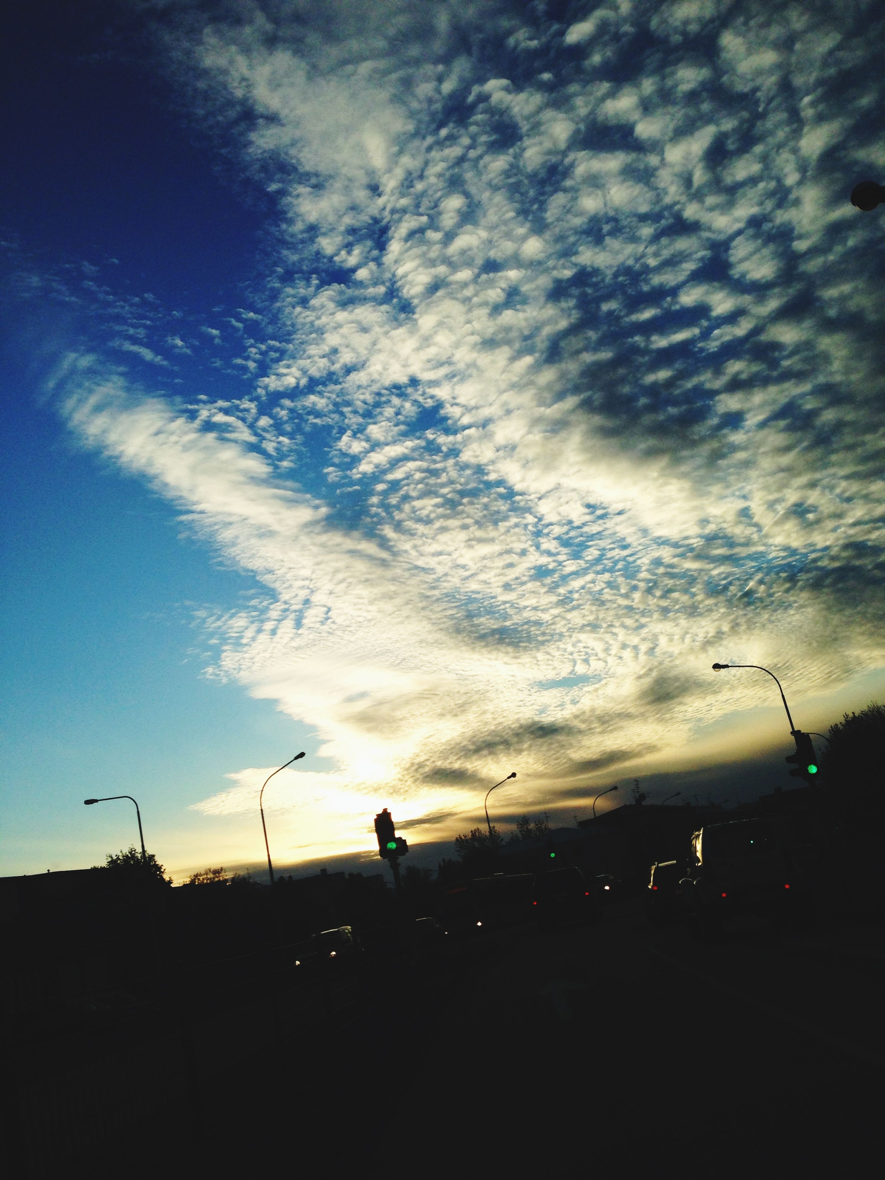 sky, transportation, cloud - sky, silhouette, mode of transport, cloudy, street light, road, car, cloud, dusk, airplane, land vehicle, low angle view, street, on the move, weather, air vehicle, road marking, sunset