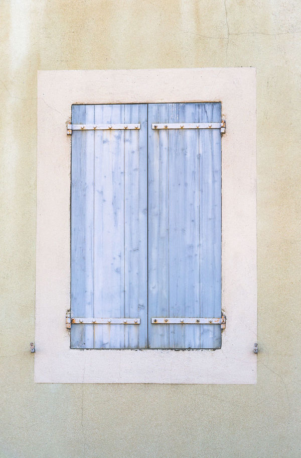 Closed widow covered with rustic wooden light blue shutters in Carcassonne, Frane Architecture Building Exterior Built Structure Central Point Closed Closed Door Corners Cream Colour Divide Edges Light Light Blue Minimalistic Old Plant Rectangle Rustic Shutters Simple Vintage Wall Elevation Window Wooden
