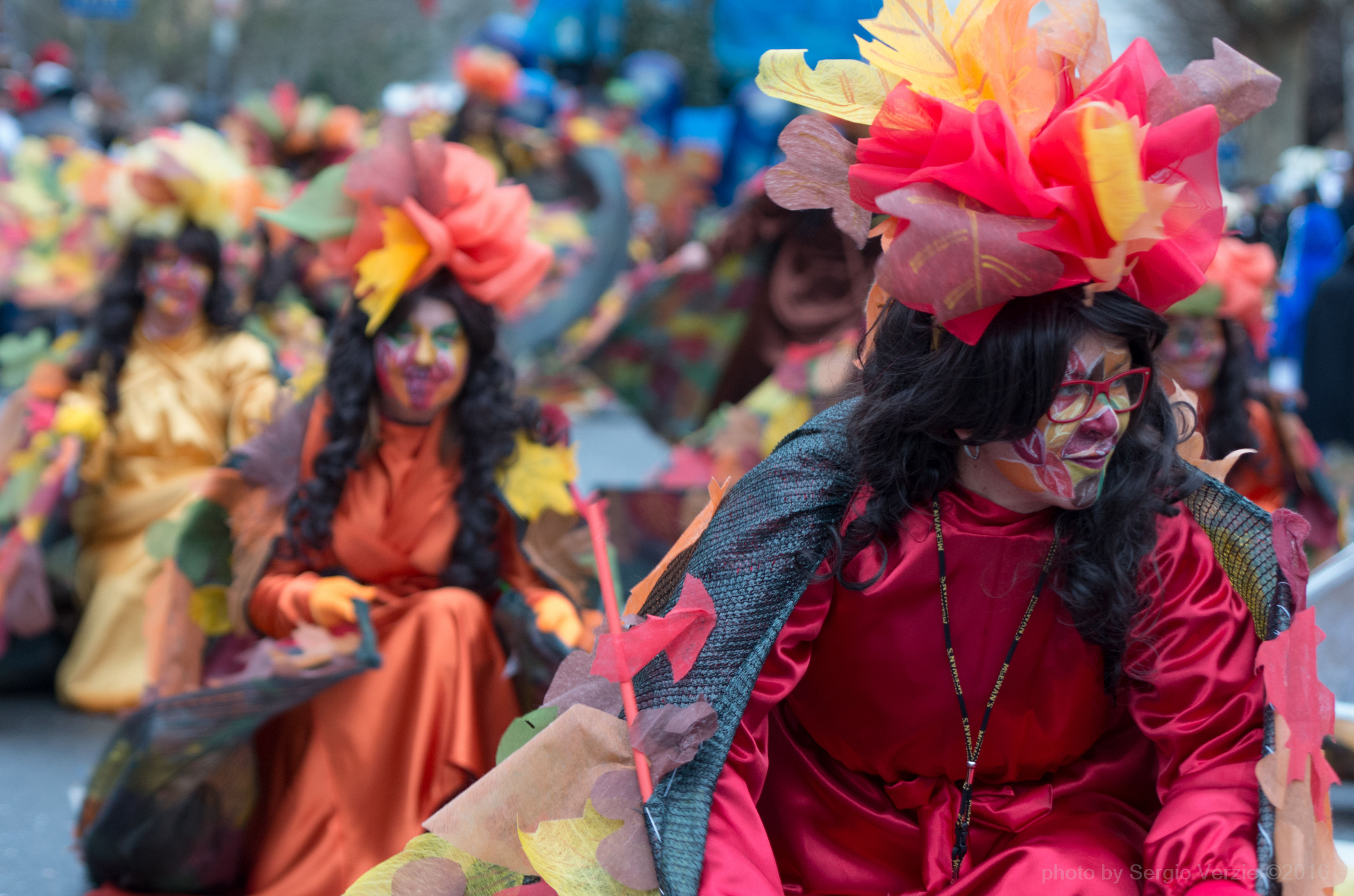 focus on foreground, flower, lifestyles, person, leisure activity, traditional clothing, men, celebration, cultures, large group of people, multi colored, tradition, day, close-up, red, incidental people, outdoors, costume, religion