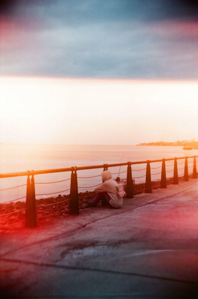 坐在岸邊對著淡水河發呆的女生。 DIY雙反相機 燒底片 街拍