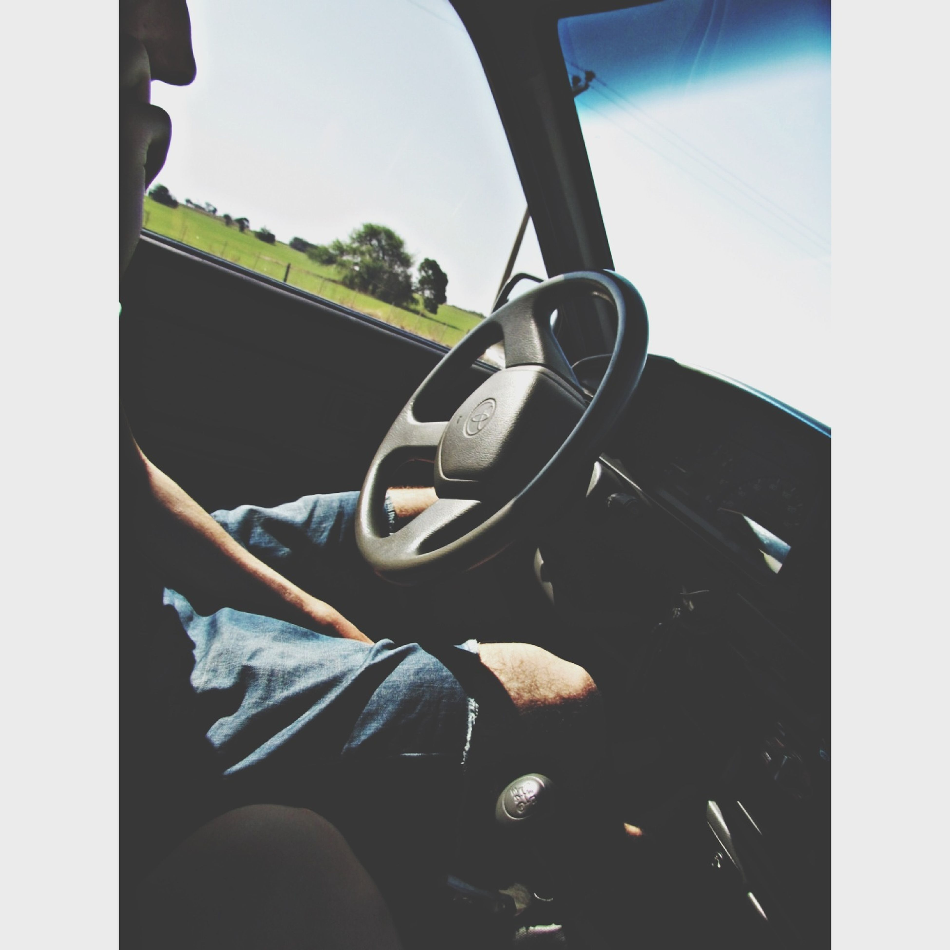 transportation, mode of transport, land vehicle, transfer print, lifestyles, auto post production filter, leisure activity, sunlight, men, day, car, sitting, window, indoors, technology, part of, holding, vehicle interior