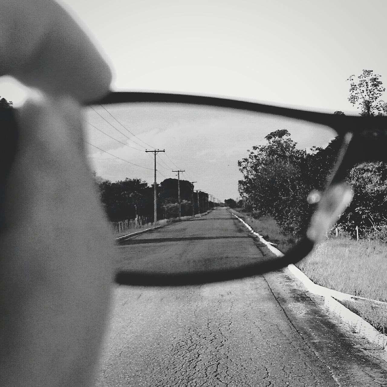 Cropped Image Of Hand Holding Eyeglasses Against Country Road