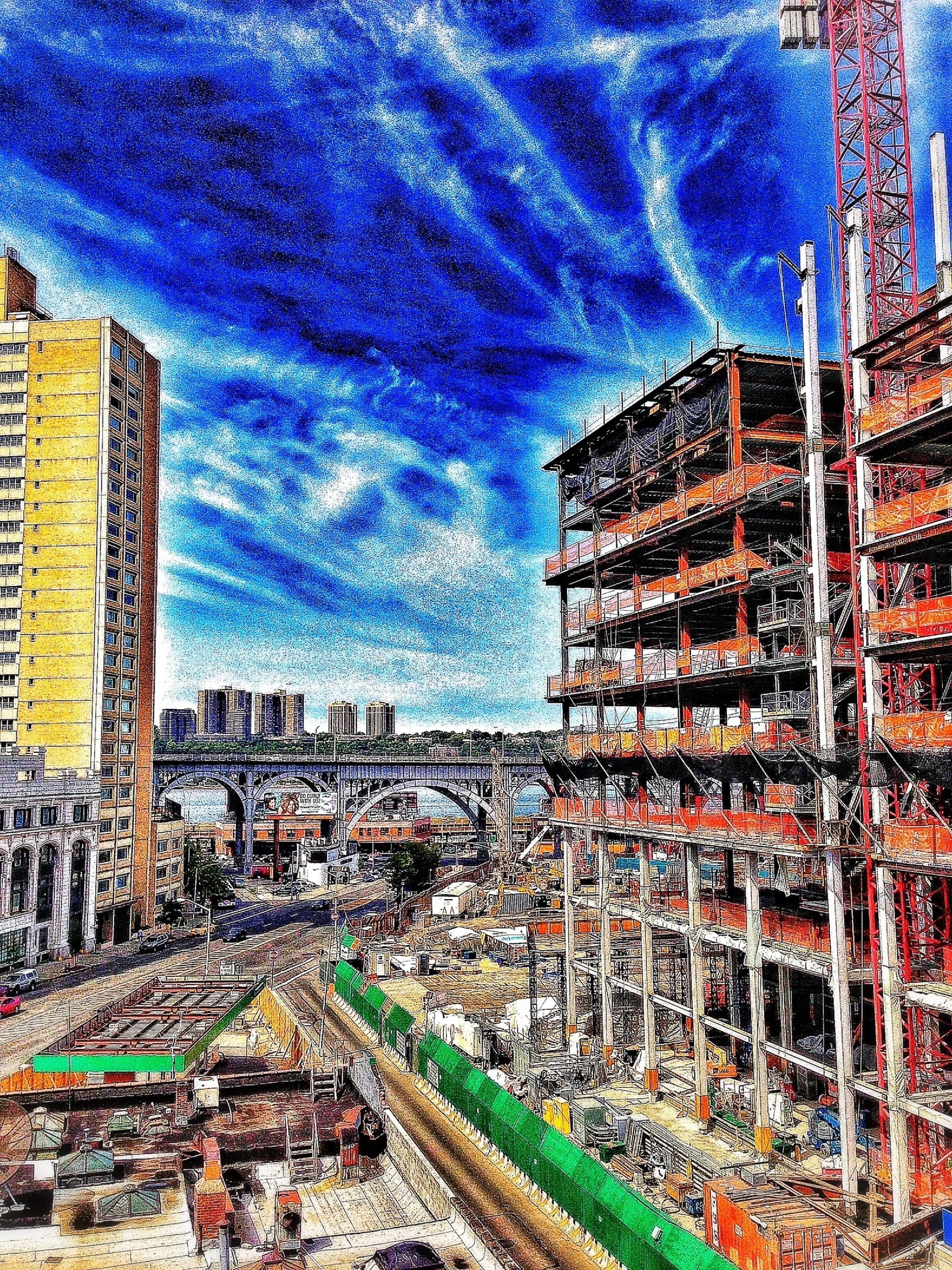 building exterior, architecture, built structure, city, sky, cloud - sky, cityscape, high angle view, cloudy, city life, residential building, street, outdoors, residential district, cloud, development, residential structure, construction site, road, transportation