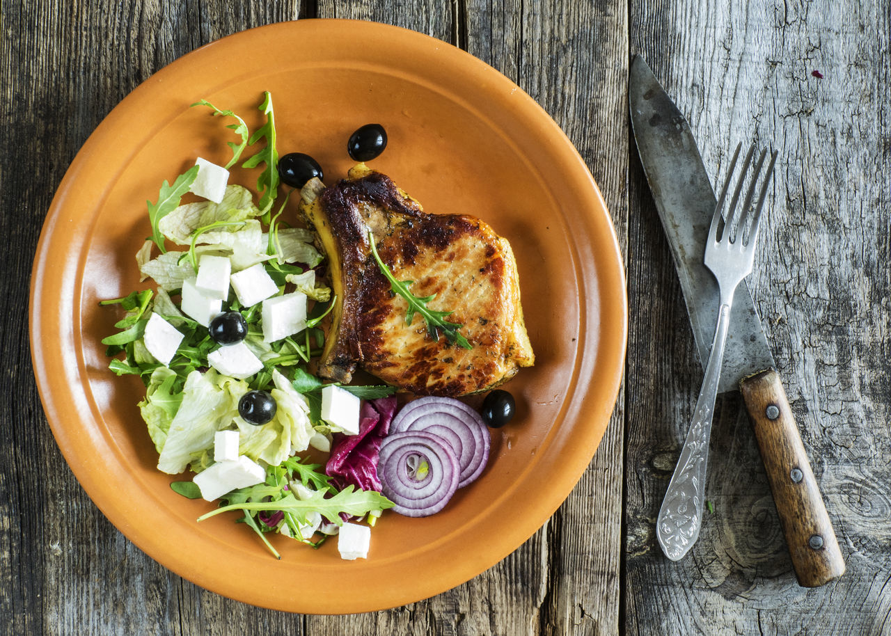 Roasted pork chop on a plate with a green salad, red onion on an old wooden weathered table Chop Directly Above Food Green Healthy Eating Main Course Meal Meat No People Old Onion Plate Pork Ready-to-eat Relaxing Roast Chicken Roasted Salad Table Weathered Wood - Material Wooden