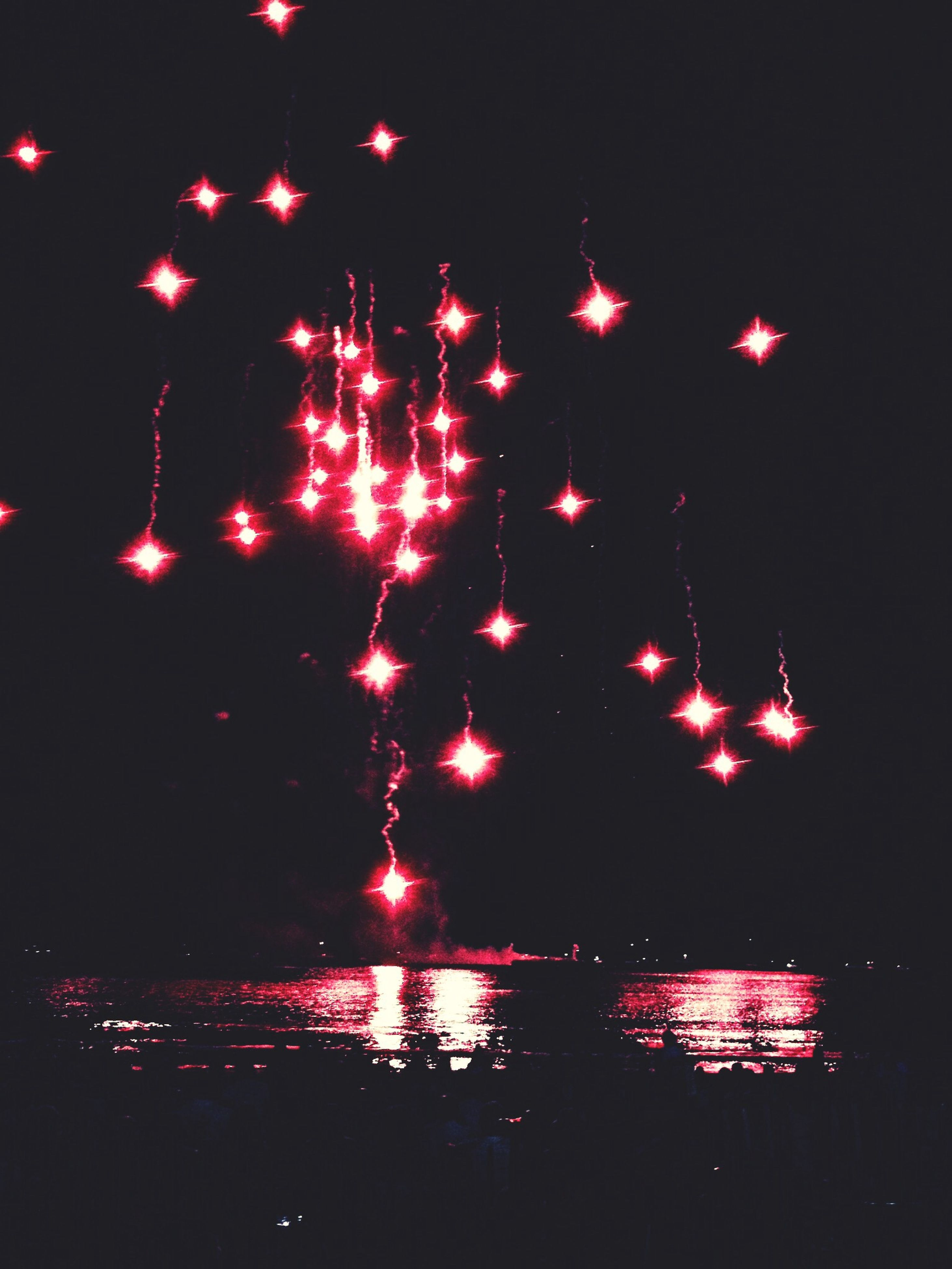 night, illuminated, water, celebration, glowing, firework display, motion, arts culture and entertainment, long exposure, event, sky, reflection, exploding, firework - man made object, multi colored, sea, red, waterfront, outdoors, dark