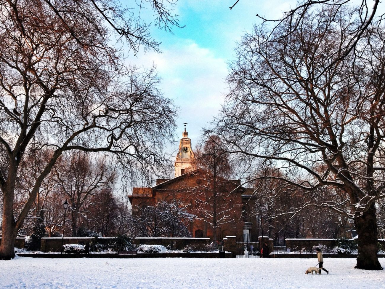 A lady walks her dog through the snow-covered St John's Gardens in Hackney, London.