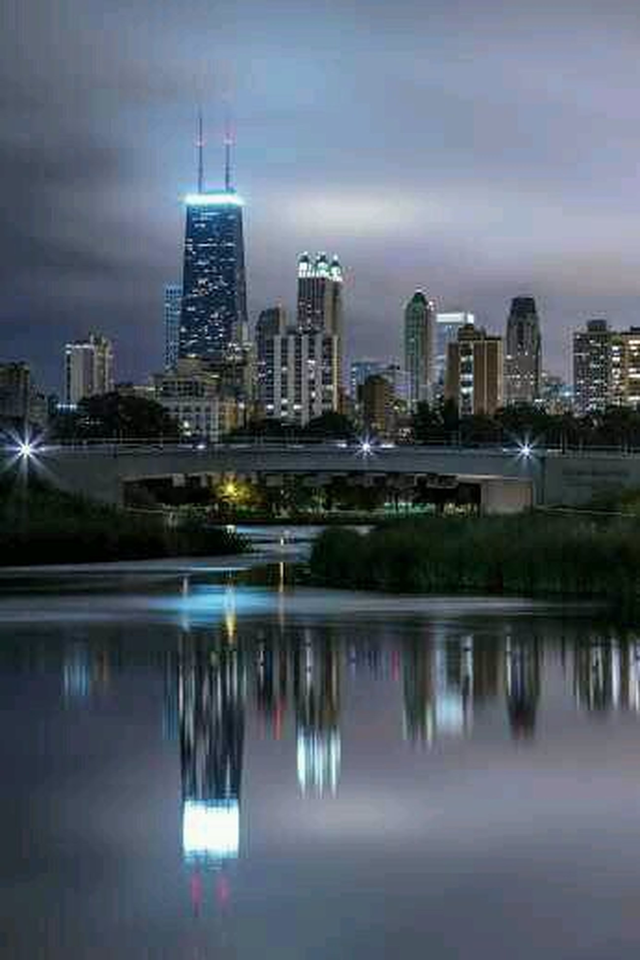 building exterior, city, architecture, skyscraper, built structure, cityscape, water, waterfront, illuminated, urban skyline, reflection, modern, sky, office building, tall - high, river, tower, financial district, night, skyline