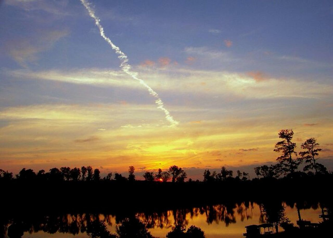 vapor trail, silhouette, sunset, nature, sky, scenics, beauty in nature, tree, no people, cloud - sky, outdoors, contrail, landscape, day